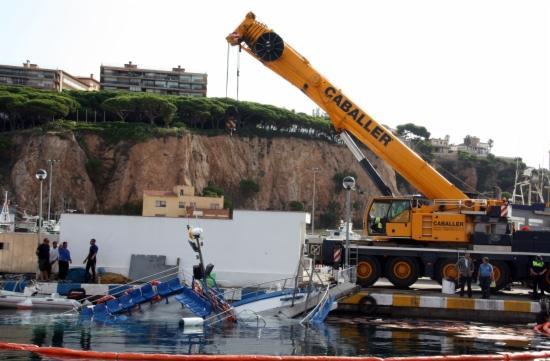 Una grua reflota el vaixell enfonsat al port de Sant Feliu