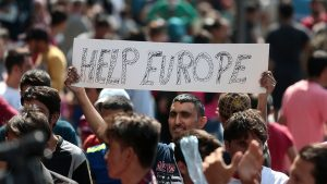 """A man hold a placard reading """"Help Europe"""" as Syrian and Afgan refugees attend a protest rally to demand to travel to Germany on September 2, 2015 outside the Keleti (East) railway station in Budapest. Hungarian authorities face mounting anger from thousands of migrants who are unable to board trains to western European countries after the main Budapest station was closed.  AFP PHOTO / FERENC ISZA        (Photo credit should read FERENC ISZA/AFP/Getty Images)"""