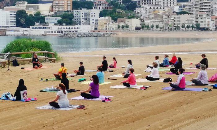 Tornen les classes de ioga gratuïtes a la platja gran de Sant Feliu i a Sant Pol